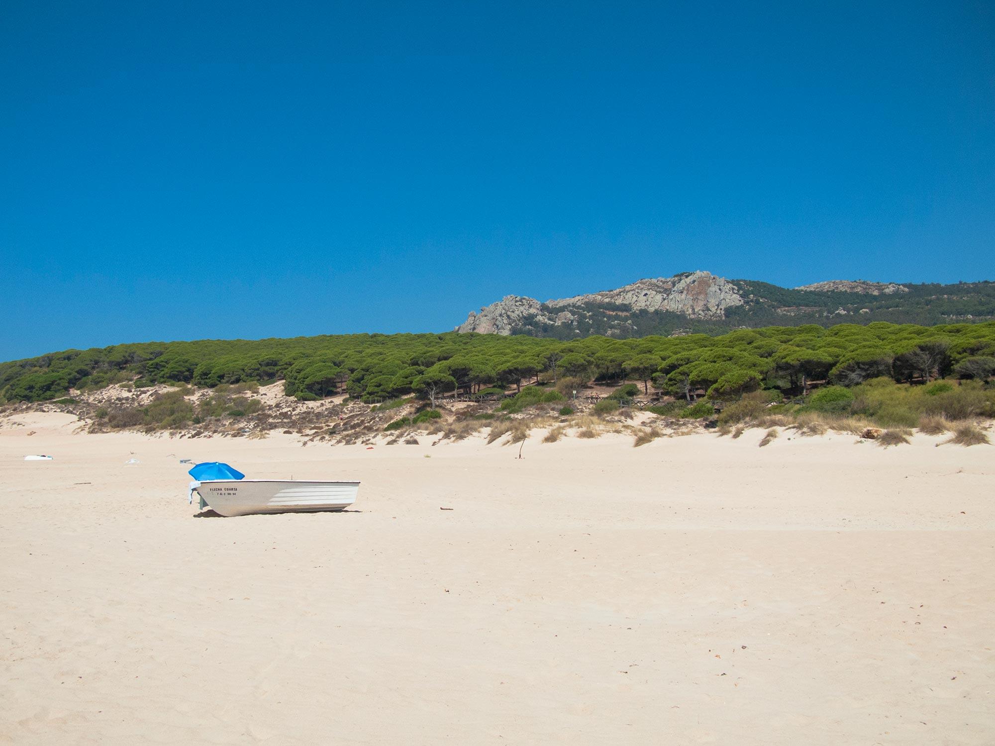Bolonia beach boat and blue umbrella