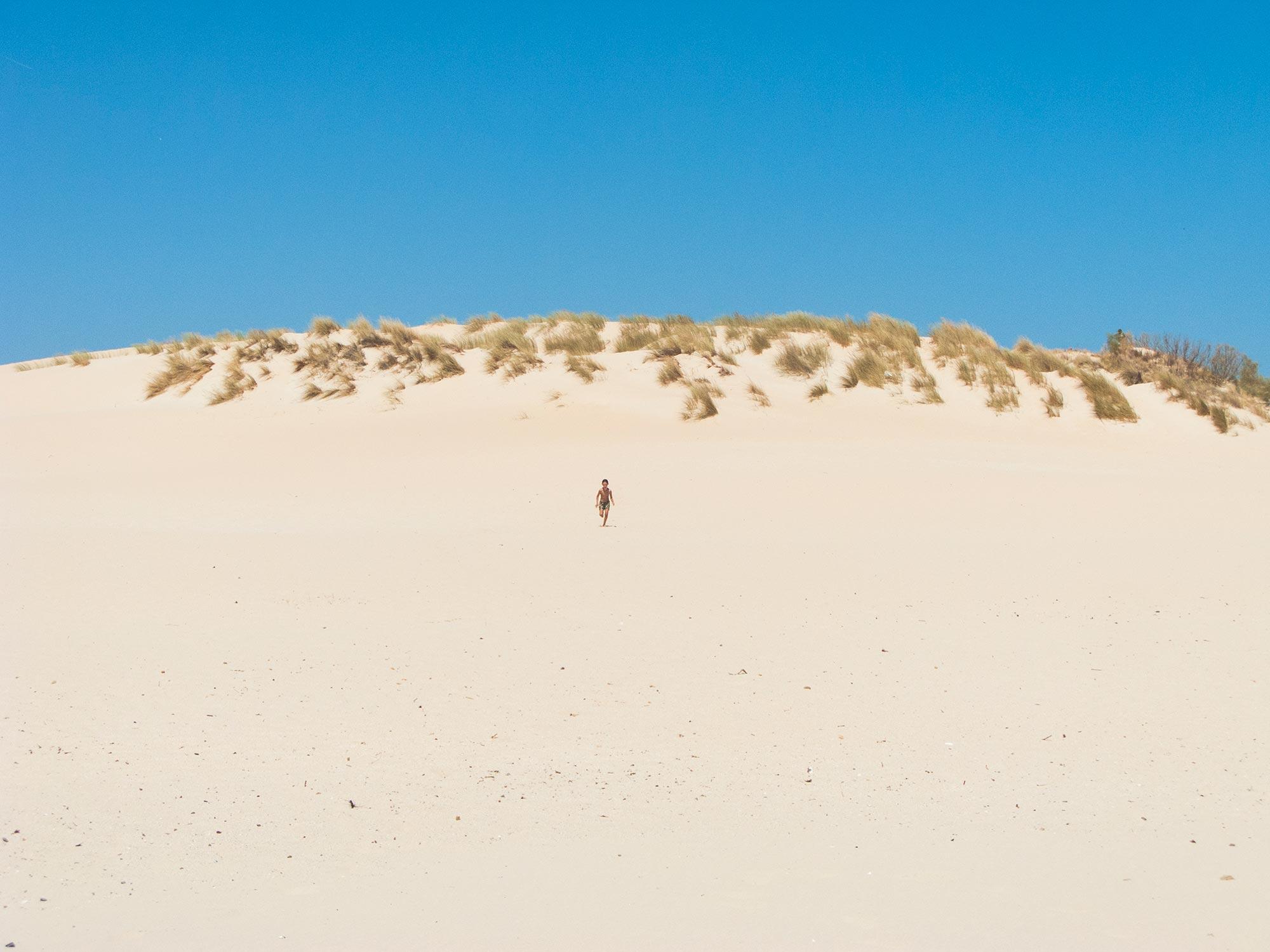 valdevaqueros beach kid running on a dune